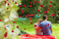 Composite image of loving couple admiring nature while leaning on their cabriolet Royalty Free Stock Image