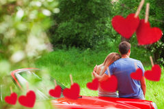 Composite image of loving couple admiring nature while leaning on their cabriolet. Loving couple admiring nature while leaning on their cabriolet against hearts Royalty Free Stock Photos