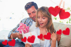 Composite image of loving couple with flowers and greeting card. Loving couple with flowers and greeting card against hearts hanging on a line Royalty Free Stock Images