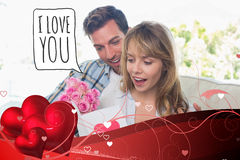 Composite image of loving couple with flowers and greeting card Royalty Free Stock Photography