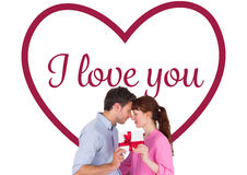 Composite image of loving couple holding a gift. Loving couple holding a gift against valentines love hearts stock photos