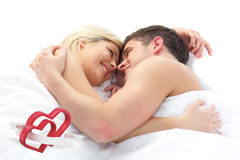 Composite image of loving couple relaxing on bed. Loving Couple relaxing on bed  against linking hearts Stock Photo