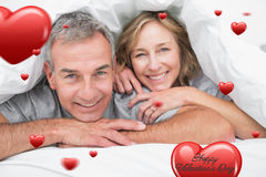 Composite image of loving couple under the duvet Stock Images