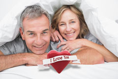 Composite image of loving couple under the duvet Royalty Free Stock Image