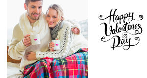 Composite image of loving couple in winter clothing with coffee cups against window Royalty Free Stock Image