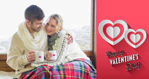 Composite image of loving couple in winter wear with cups against window Royalty Free Stock Image