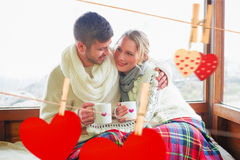Composite image of loving couple in winter wear with cups against window. Loving couple in winter wear with cups against window against hearts hanging on the Stock Photo