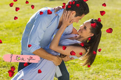 Composite image of loving and happy couple dancing in park. Loving and happy couple dancing in park against i love you stock images