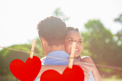Composite image of loving and happy woman embracing man at park. Loving and happy women embracing men at park against hearts hanging on a line Stock Images