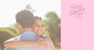 Composite image of loving and happy woman embracing man at park Stock Photo