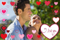 Composite image of loving and happy young couple at park. Loving and happy young couple at park against valentines love hearts royalty free stock image