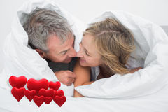 Composite image of loving middle aged couple under the duvet. Loving middle aged couple under the duvet against love hearts Royalty Free Stock Photo