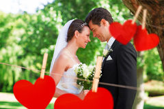 Composite image of loving newly wed couple in garden Stock Photos