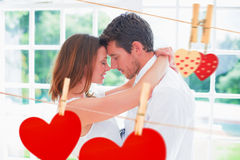 Composite image of loving young couple with arms around. Loving young couple with arms around against hearts hanging on the line Stock Photo