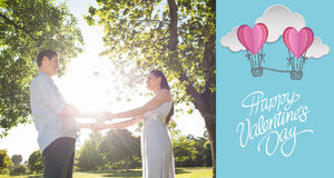 Composite image of loving young couple holding hands at park. Loving young couple holding hands at park against cute valentines message Royalty Free Stock Photos
