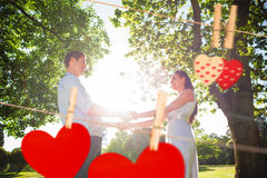 Composite image of loving young couple holding hands at park. Loving young couple holding hands at park against hearts hanging on the line Stock Photography