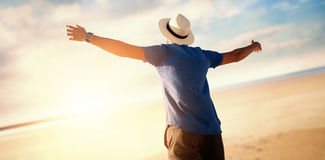 Composite image of low angle of a man raising arms up. Low angle of a man raising arms up  against serene beach landscape Stock Photo