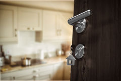 Composite image of low angle view of brown door with house key. Low angle view of brown door with house key against kitchen interior Stock Image