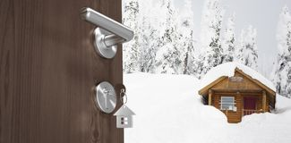 Composite image of low angle view of brown door with house key. Low angle view of brown door with house key against little wood house in the snow Stock Photography