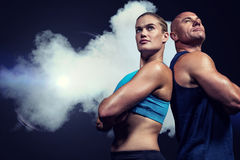 Composite image of low angle view of muscular man and woman royalty free stock photo