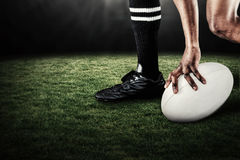 Composite image of low section of athlete holding ball while running Stock Photo