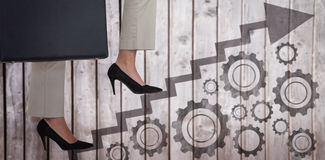 Composite image of low section of businesswoman climbing steps with briefcase royalty free stock image