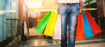 Composite image of low section of man carrying colorful shopping bag Stock Images