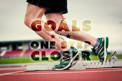 Composite image of low section of a man ready to race on running track. Low section of a man ready to race on running track against goals one step closer Royalty Free Stock Images