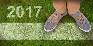 Composite image of low section of man wearing shoes. Low section of man wearing shoes  against closed up view of grass Royalty Free Stock Photos