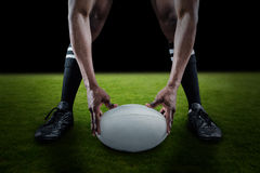 Composite image of low section of sportsman holding ball while playing rugby Stock Photography