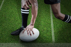 Composite image of low section of sportsman holding rugby ball Royalty Free Stock Images