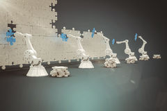 Composite image of machineries arranging blue jigsaw piece on puzzle 3d. Machineries arranging blue jigsaw piece on puzzle against blue vignette background 3d Stock Photography