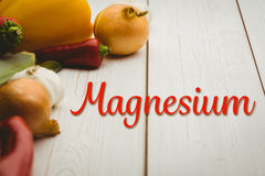Composite image of magnesium. Magnesium against vegetables on wooden table Royalty Free Stock Images