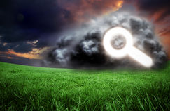 Composite image of magnifying glass in cloud. Against green field under orange sky Stock Image