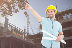 Composite image of male architect with blueprints pointing away Royalty Free Stock Image