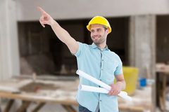 Composite image of male architect with blueprints pointing away Royalty Free Stock Photography