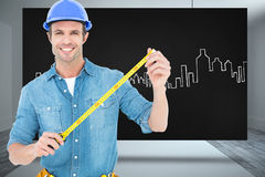 Composite image of male architect holding tape measure. Male architect holding tape measure against composite image of black card Royalty Free Stock Photo