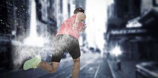 Composite image of male athlete running from starting blocks. Male athlete running from starting blocks against white dust powder Royalty Free Stock Photography