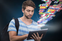 Composite image of male college student using digital tablet. Male college student using digital tablet against blue background with vignette Royalty Free Stock Images