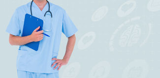 Composite image of male doctor holding clipboard and pen with hand on hip Royalty Free Stock Image
