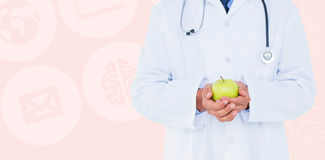 Composite image of male doctor holding green apple Stock Photos
