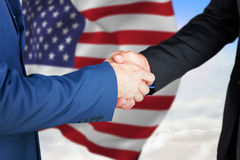 Composite image of male executives shaking hands. Male executives shaking hands against blue sky with white clouds stock photo