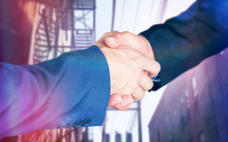 Composite image of male executives shaking hands. Male executives shaking hands against electric cables and building exterior royalty free stock photos
