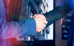 Composite image of male executives shaking hands. Male executives shaking hands against exterior of modern building royalty free stock photos