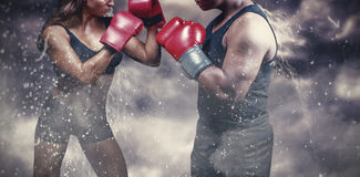 Composite image of male and female boxer with fighting stance. Male and female boxer with fighting stance against digitally generated image of color powder stock image