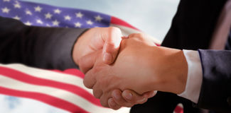 Composite image of male and female corporates shaking hands. Male and female corporates shaking hands against composite image of low angle view of american flag Royalty Free Stock Photos