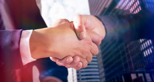 Composite image of male and female corporates shaking hands. Male and female corporates shaking hands against view of modern office building Stock Images