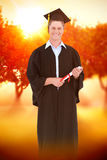 Composite image of a male graduate with his degree in hand Royalty Free Stock Photography