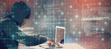 Composite image of male hacker using laptop on table Royalty Free Stock Image