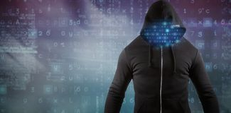 Composite image of male hacker wearing black hoodie while standing. Male hacker wearing black hoodie while standing against turquoise and purple background Royalty Free Stock Photography